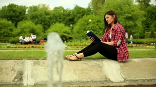 Young beautiful woman reading a book sitting in the park