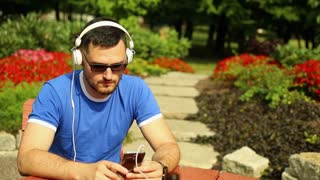 Young man is listening music on smartphone in the park