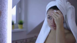 Young, pretty woman in bathrobe make up on face  in bathroom