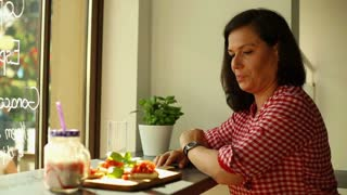 Young woman eat and looking out the window in restaurant