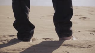 Male feet walking on sand