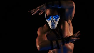 Man in a mask of a skull and glasses dance on black background
