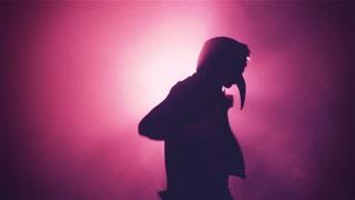 Man in mask dancing in smoke