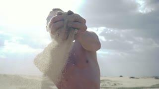 Man pours sand through his fingers