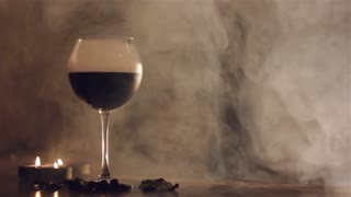 Red wine in glass with dry ice on smoke background