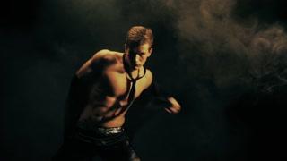 Sexy man dance on black background