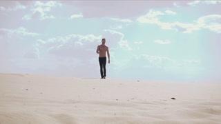 Sexy man walk in desert