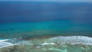 Aerial view of endless turquoise azure indian ocean swash and surfing waves
