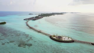Aerial view of tropical island resort hotel with white sand palm trees and turquoise Indian ocean on Maldives, drone footage from above in 4k
