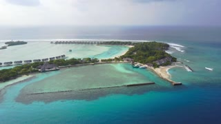 Aerial view of tropical island resort hotel with white sand palm trees and turquoise Indian ocean on Maldives, drone footage from above