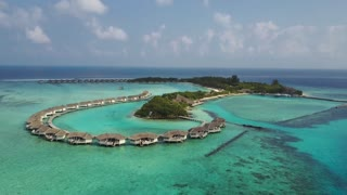 Aerial view of tropical island resort hotel with white sand palm trees and turquoise Indian ocean on Maldives