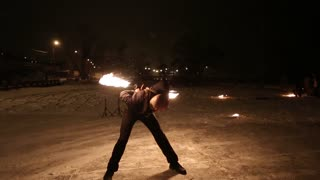 Amazing tribal fire show dance at night on winter under falling snow. Dance group performs with torch lights and pyrotechnics on snowy weather.