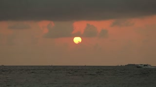 Beautiful sunset over ocean. Speed boat riding on waves on horizon. Red sun glow reflecting in the water. Clouds in the sky. Rising sun on sunrise.