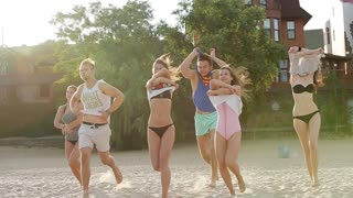 Group of friends undress running into the sea water on sunset and throw shirts on the beach. Cheerful happy people having fun on the beach. Men and women go to swim in slow motion.