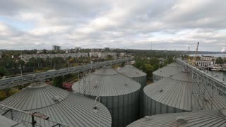 Modern grain terminal panorama. Metal tanks of elevator. Grain-drying complex construction. Commercial grain or seed silos at seaport. Steel storage for agricultural harvest. Clouds floating in sky.