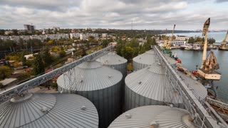 Modern grain terminal timelapse. Metal tanks of elevator. Grain-drying complex construction. Commercial grain or seed silos at seaport. Steel storage for agricultural harvest. Clouds floating in sky.