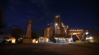 Night panorama of loading grain crops on bulk freighter ship via trunk to open cargo holds at silo terminal in seaport from trucks. Cereals bulk transshipment. Transportation agricultural products.