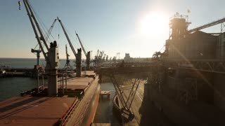 Panorama of grain terminal at seaport on sunny day. Cereals bulk transshipment to vessel loading grain crops on bulk ship from large elevators at the berth. Transportation of agricultural products.
