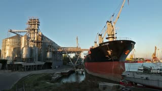 Panorama of grain terminal at seaport on sunny evening. Cereals bulk transshipment to vessel loading grain crops on bulk ship from large elevators at the berth. Transportation of agricultural products