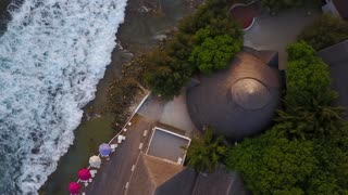 Top view of Maldives island, camera is rising over the bar at luxury tropical hotel resort. Drone ascending over the restraunt showing huge surf and big waves from above. Aerial fooage of swash
