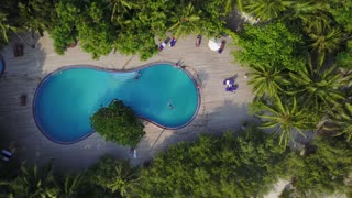 Top view of Maldives island, camera is rising over the swimming pool on luxury hotel. Aerial video of resort with lots of palms, bungalows, beach and indian ocean. View from above