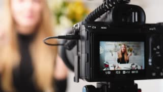 Vlogger female applies lipstick on lips. Beauty blogger woman filming daily makeup routine tutorial at camera on tripod. Influencer blonde girl live streaming cosmetics product comparison in studio
