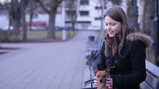Teen girl and a little angry terrier playing in a park. 60 to 24fps