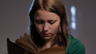 Teen girl is surrounded by books and reading. 4K UHD