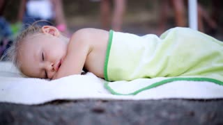 A little girl Sleeping in during family outdoor activities. Cute baby sleeps.