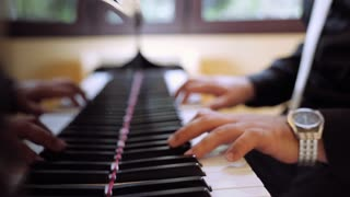 A man in tuxedo plays classical music at the restaurant on the piano. Close-up of the pianist's hands. 4K (UHD).