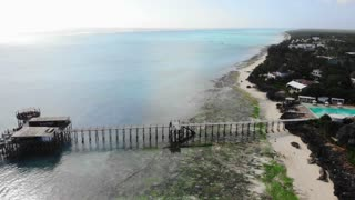 Aerial view of African wooden house with thatched roof and pier bridge on stilts. Zanzibar beach line after the tide of the ocean. Tanzania, Oceania, 4k UHD.