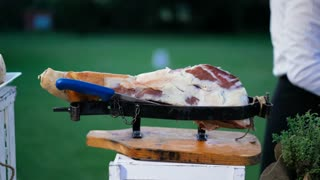 An experienced chef cutting ham with knife. Expert caterer slicing ham - Typical European food. Food service worker. 4K