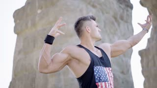 Athlete posing in the park and showing his defined muscles