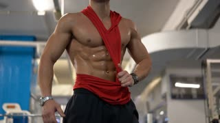 Attractive caucasian bodybuilder is at the gym after exhausting training. Strong man with sexy muscular body dressed in red t-shirt posing on the camera