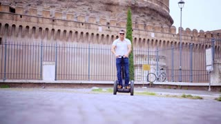 Attractive man travel on segway - urban street in the city. Tourist fun in the summer vacation. Italian tourism.