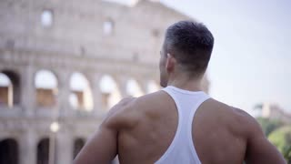 Attractive model man standing outdoors and watching ancient Roman architecture. Lifestyle and tourism conception