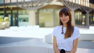 Attractive woman looking at the camera and smiling while standing at modern business center