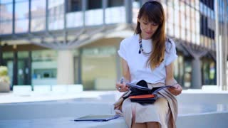 Attractive woman working on bench in the office building. Business woman working with documents.