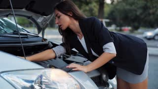Attractive women stranded with broken car on the road after car incident at night time. Broken down car concept.