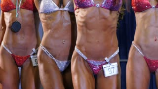 Attractive young womans demonstrating perfect fit bodies in bodybuilding championship. Sport competition, lifestyle and people concept.
