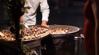 Baked chestnut at sale. European street food concept. 4K (UHD).
