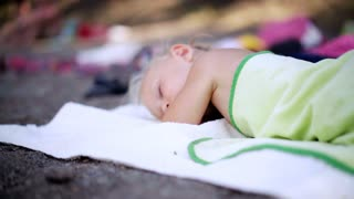 Beautiful baby girl sleeping in summertime relaxing. Child asleep on a white blanket is covered with a soft green towel.