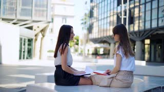 Beautiful business women talk about a concluded contract at lunchtime near the office building. Business concept. Fashionable Women sit and have informal meeting.
