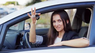 Beautiful female driver in a car showing the car key. Woman win or buy a new modern car and take joy. 4K UHD.