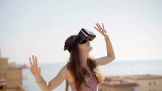 Beautiful young woman playing game in virtual reality glasses. Future is right now. Female touch something using modern virtual reality glasses. Technology and innovation