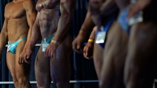 Bodybuilders model demonstrating fit bodies at fitness competition.