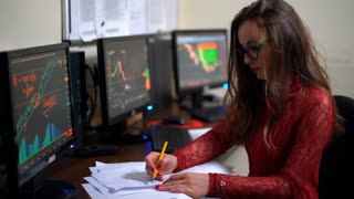 Brunette financial advisor working with documents on the background of monitors full of diagrams. World stock market. Shot in 4K (UHD).
