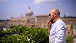 Business man standing on the terrace with cellphone, crane shot. Italian cityscape