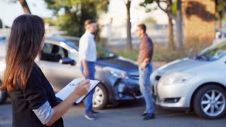 Car accident scene with wrecked car and Insurance person inspects the damage on a car and makes notes.
