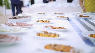 Catering event. Catering food set on table in event party in summer time. Groups of people takes delicious food from the buffet table. 4K (UHD).
